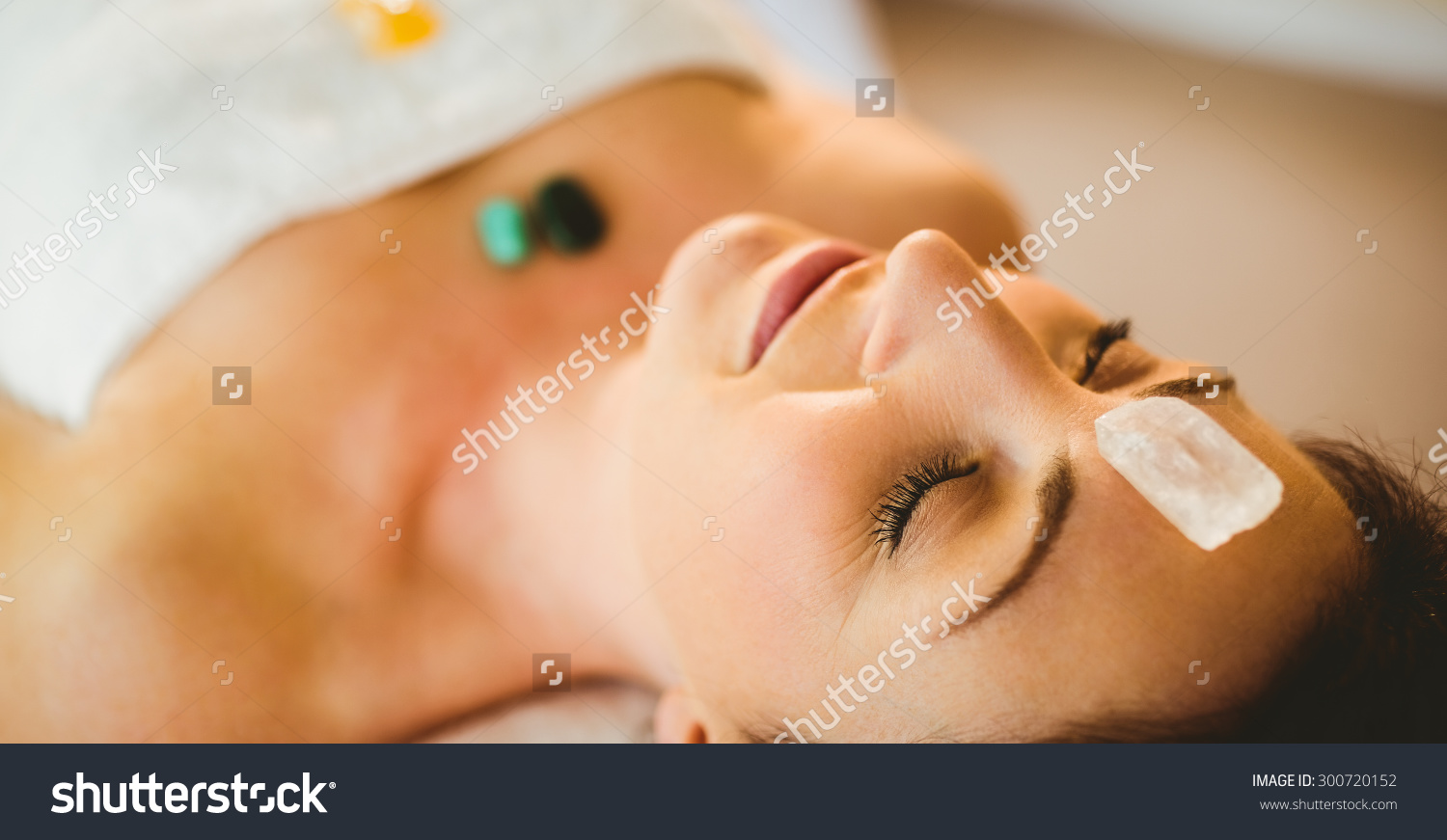 stock-photo-young-woman-at-crystal-healing-session-in-therapy-room-300720152